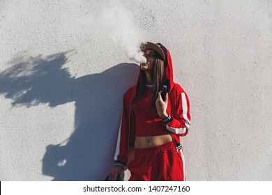 Vaping girl. Young woman standing in front of a white wall and vape e-cig. Pretty young female in black hat, red clothing vape ecig, vaping device at the sunset. Toned image. Hip-hop style.