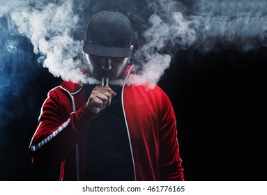 vaping man holding a mod. A cloud of vapor. Black background.