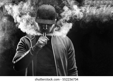 vaping man holding a mod. A cloud of vapor. Black background