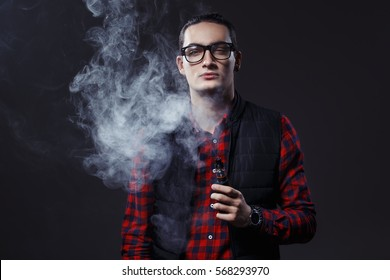 Vaping man holding a mod. A cloud of vapor. Stylish hipster with vape. Black background.