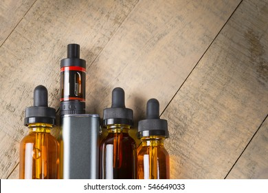 Vaping mod e-cig with tank atomizer and juice bottles over wood background