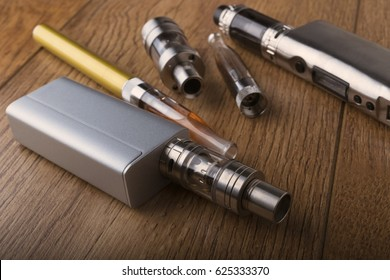 Vaping pen, vape devices, mods for electronic cigarette or e cigarette, e cig, on a wooden background.