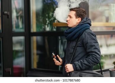 Vaping. Portrait of man vaping a vaporizer outdoors. Safe smoking. Young vaper. Close-up.