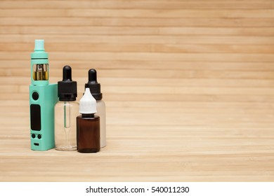 Vaping set on the wooden table with vapor. Space for text.