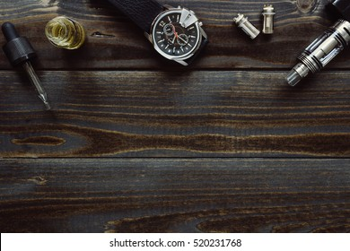 Vaping set and watch on the dark table. Hipster or bussinesman style. Modern objects with copy space on the wooden background