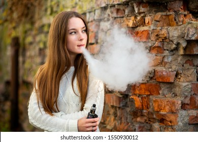 Vaping teenager. Young pretty white caucasian teenage girl with problem skin smoking an electronic cigarette the ruined brick wall on the street in the autumn. Bad habit. Vape activity.