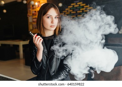 Vaping. Young beautiful girl smoking ( vaping ) e-cigarette with smoke in resturan. Vapor concept.