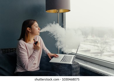 Vaping. Young beautiful woman smoking ( vaping ) e-cigarette and work on laptop. Vapor concept. Electronic cigarette with working