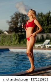 Vapor concept. Sexy woman in red lingerie vaping. A cloud of vapor. Sexy girl with cool body vaping near pool and releases a cloud of vapor.