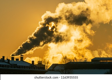 The vapor thick from the cold and illuminated by a huge low sun rising above the historical center of St. Petersburg