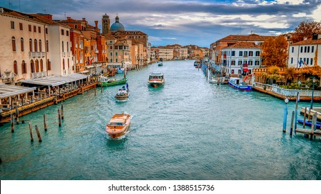 Vaporetto and commercial boats traverse the Grand Canal in Venice, Italy, faces and logos blurred for commercial use