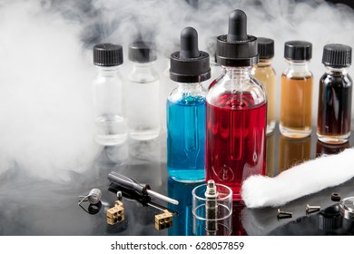 Vaporizer smoke with juice bottles, screwdriver and cotton wick with tools
