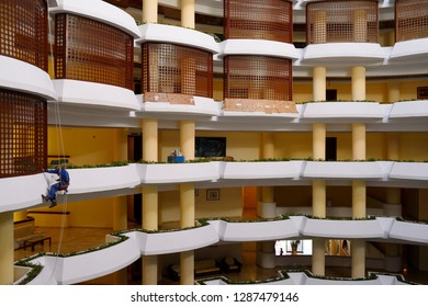 Varadero, Cuba - April 3, 2014: Workman painting balconies of inner open air atrium at a Varadero resort hotel