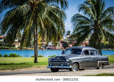 VARADERO, CUBA - JULY 03, 2015: HDR Grey green american vintage car parked under palms in Varadero Cuba