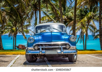 Varadero, Cuba - June 21, 2017: HDR - American blue Chevrolet classic car with white roof parked under palms in Varadero Cuba - Serie Cuba Reportage
