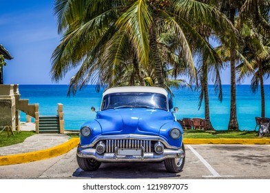 Varadero, Cuba - June 21, 2017: HDR - American blue Buick classic car parked under palms on the beach in Varadero Cuba -Serie Cuba Reportage