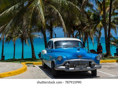Varadero, Cuba - June 21, 2017: American blue Buick Eight classic car parked under palms on the beach in Varadero Cuba -Serie Cuba Reportage