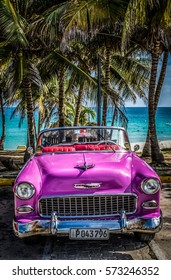 VARADERO, CUBA - JUNE 22, 2015: HDR - 1955 pink american Chevrolet Bel air Cabriolet classic car park under palms on the beach in Varadero Cuba - Serie Cuba Reportage