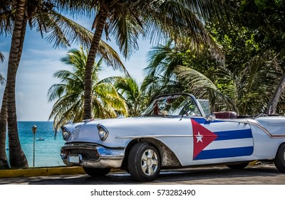 VARADERO, CUBA - JUNE 22, 2015: HDR - American white Chevrolet cabriolet vintage car with cuban flag on the side door parked under palms near the beach - Serie Cuba Reportage