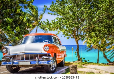 Varadero Cuba - June 24, 2017: HDR - Parked american white orange Ford Fairlane vintage car in the front view and with a relaxed cuban man on the beach in Varadero Cuba - Serie Cuba Reportage