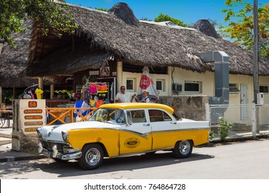 Varadero Cuba - June 24, 2017: American white yellow Ford Fairlane vintage car parked before a tourists store in Varadero Cuba - Serie Cuba Reportage