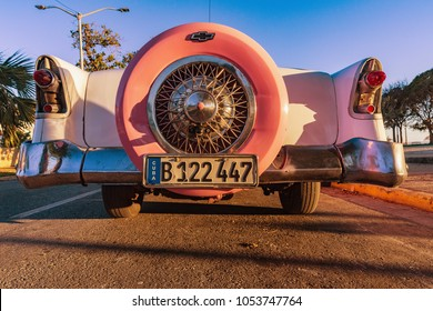 VARADERO, CUBA - MARCH 3, 2018: Pink american Chevrolet Oldtimer parked near the beach under palms, Cuba, Varadero. Spare wheel on pink Chevrolet