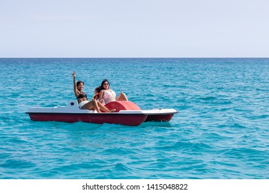 Varadero, Cuba - May 11, 2019: Cuban Family are having fun on a pedal board in the ocean during a vibrant and bright sunny day.