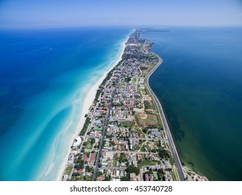 VARADERO, CUBA - MAY 25, 2016: Drone flies over tropical island. Calm Atlantic Ocean and the bay. It is flying over the city. Cars are riding on the road closely to the shore. Height of 500 meters