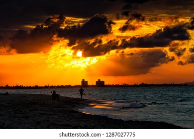 VARADERO, CUBA - NOVEMBER 28, 2017: The famous beach of Varadero in Cuba with a calm turquoise ocean and clouds in the sky. Sunset time