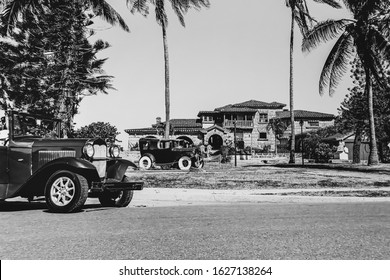Varadero, Cuba. November 29, 2019: American vintage retro car parked on the road on background ancient castle. black and white photo