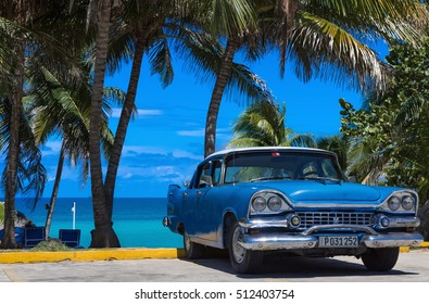 Varadero, Cuba - September 11, 2016: American blue Buick classic car parked on the beach under palms in Varadero Cuba - Serie Cuba 2016 Reportage