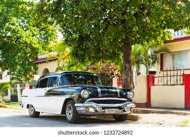 Varadero, Cuba - September 24, 2018: American black white Pontiac classic car parked in the sidestreet before a house in Varadero Cuba - Serie Cuba Reportage