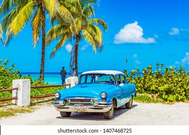 Varadero, Cuba - September 24, 2018: HDR -  Cuban people with a parked american blue 1955 Buick Roadmaster classic car direct on the beach in Varadero Cuba - Serie Cuba Reportage