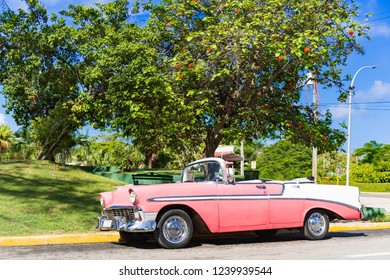 Varadero, Cuba - September 28, 2018: American rose white vintage car parked in the sidestreet in Varadero Cuba - Serie Cuba Reportage