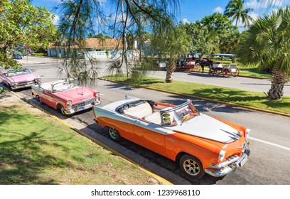 Varadero, Cuba - September 28, 2018: American convertible vintage cars parked in a row in the sidestreet from Varadero Cuba in high angle view - Serie Cuba Reportage