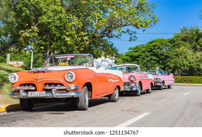 Varadero, Cuba - September 28, 2018: American Dodge, Chevrolet and Cadillac convertible vintage cars parked in a row in the sidestreet from Varadero Cuba - Serie Cuba Reportage