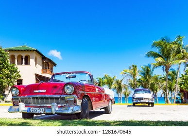 Varadero, Cuba - September 28, 2018: American red convertible 1956 Chevrolet Bel Air and a blue white 1956 Ford Fairlane vintage car parked direct on the beach in Havana Cuba - Serie Cuba Reportage