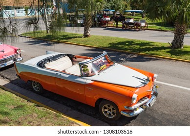 Varadero, Cuba - September 28, 2018: American orange 1955 Dodge Custom Royal and pink Chevrolet Bel air convertible and Cadillac convertible vintage cars parked in Varadero Cuba - Serie Cuba Reportage
