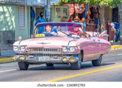 Varadero, Cuba-September 9, 2018: Pink convertible taxi. Old obsolete American car or vehicle driving in Cuban streets during daytime. Cuba is known for the variety of models it keeps running
