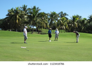 Varadero Golf Club, Cuba/ Nov 2010/ Caucasian male golf player with hat making a putt on the green of sunny golf course with four players, while other three men are waiting