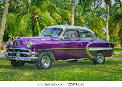 Varadero island, Cuba, Aug 20, 2014, Side view of beautiful, charming old, vintage classic car parked in tropical garden on sunny summer day