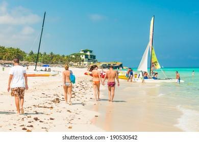 VARADERO,CUBA - APRIL 28,2014 : Tourists walking along the shore and boarding a sailing boat on a beautiful sunny day at the beach