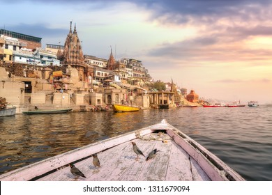 Varanasi ancient city architecture with Ganges river ghat at sunset as viewed from a boat