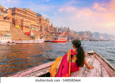 Varanasi ancient city architecture with Ganges river bank at sunset. Indian female tourist enjoy boat ride on the river Ganges