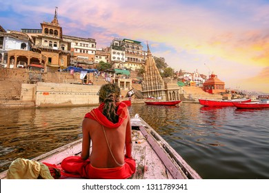 Varanasi city architecture with Ganges river bank at sunset with view of sadhu baba enjoying a boat ride on river Ganga.