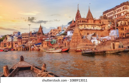 Varanasi Ganges river ghat with ancient city architecture as viewed from a boat on the river at sunset.