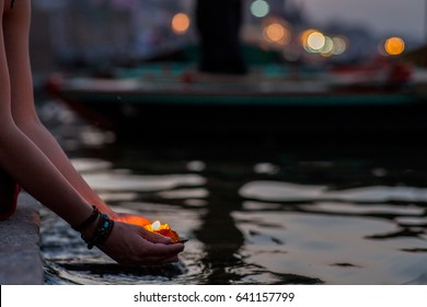 Varanasi, India – 03 15 2014: Hands of a woman doing a evening fire ritual (puja) in the river Ganges.