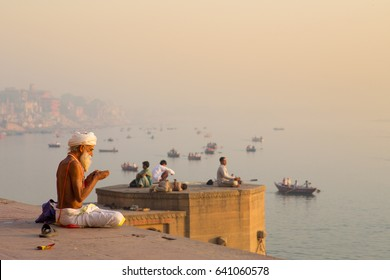Varanasi, India – 03 26 2016: A Hindu man sitting with a turban next to the holy Ganges river and praying in the sunrise.