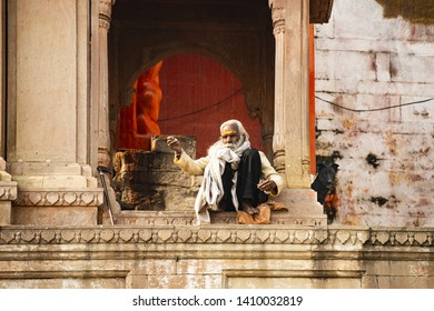 VARANASI - INDIA - 10 MARCH 2019. A Sadhu with a long white beard and his dog are sitting on a Ghat in Varanasi. Sadhu is an ascetic or someone who practices yoga. Varanasi, Uttar Pradesh, India.