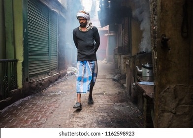 VARANASI, INDIA - 20 FEBRUARY 2015: Street tea vendor walking in front of his stall while fire boils his water.